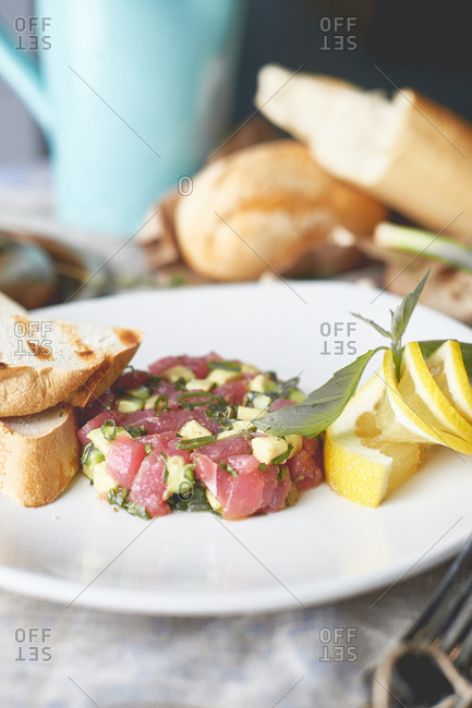 Tuna tartare with avocado and arugula with grilled toast and lemon fresh french baguette