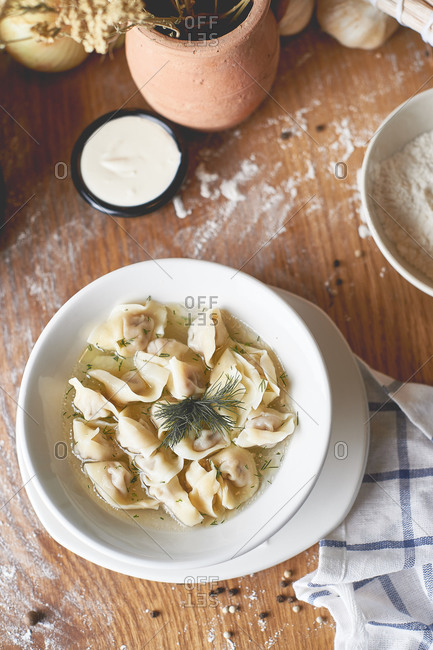 Meat dumplings Russian cuisine with broth dill sour cream