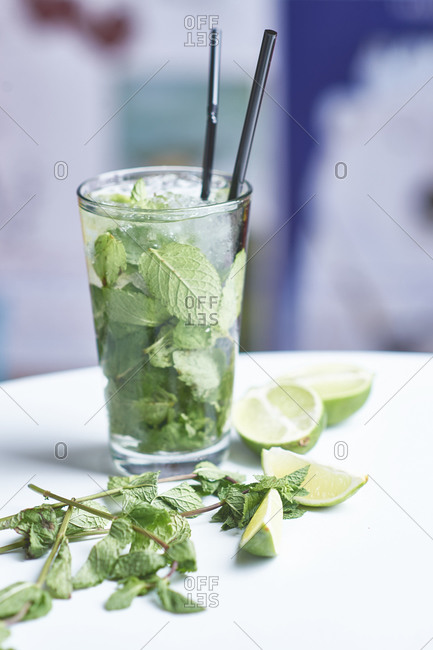 Mojito with mint and lime in a glass with a straw