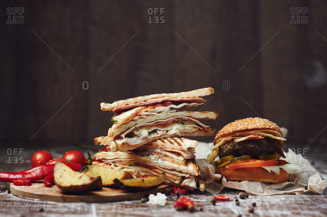 Burger with french fries and sandwich club with ham and chicken