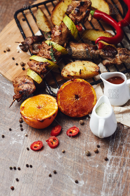 Pork kebab on a wooden skewer with vegetables and oranges with barbecue sauce pepper and french fries