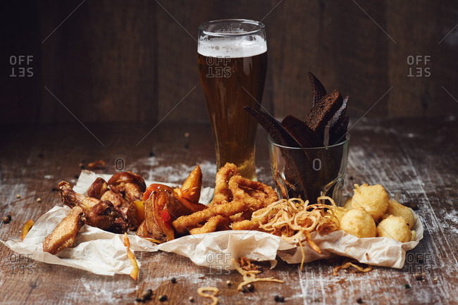 Glass of beer with chicken wings, french fries, squid rings, cheese balls, onion rings, and crackers