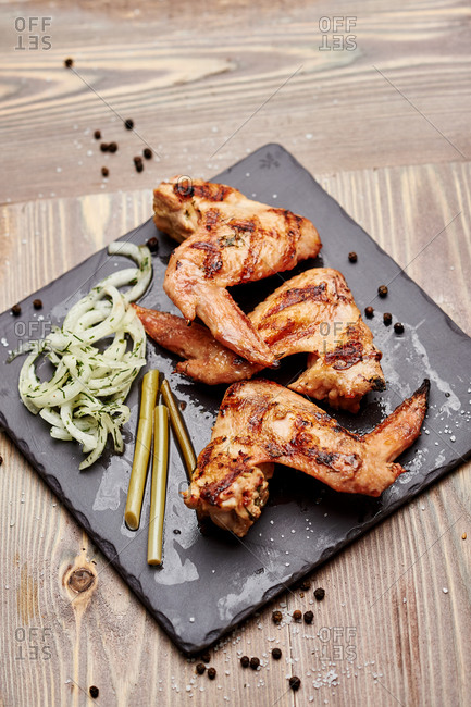 Grilled chicken wings fried on coals with pickled onions