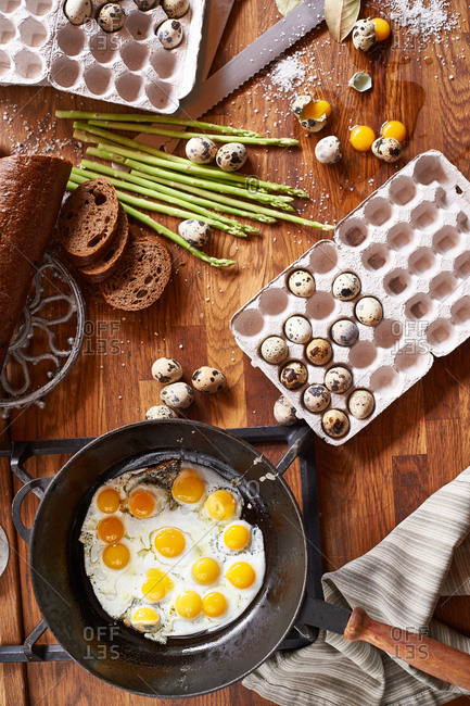 Breakfast quail eggs fried in a cast iron pan on the table
