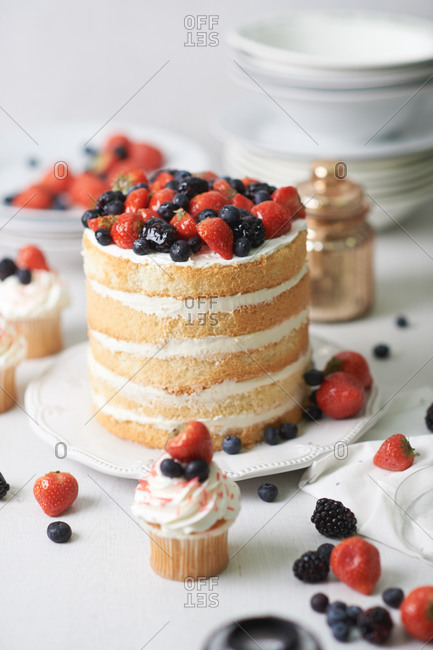 Dessert cake made of sponge cakes with white cream and strawberries, blueberries, blackberries