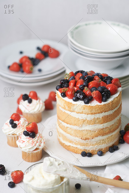 Sponge cakes with white cream, strawberries, blueberries, and blackberries