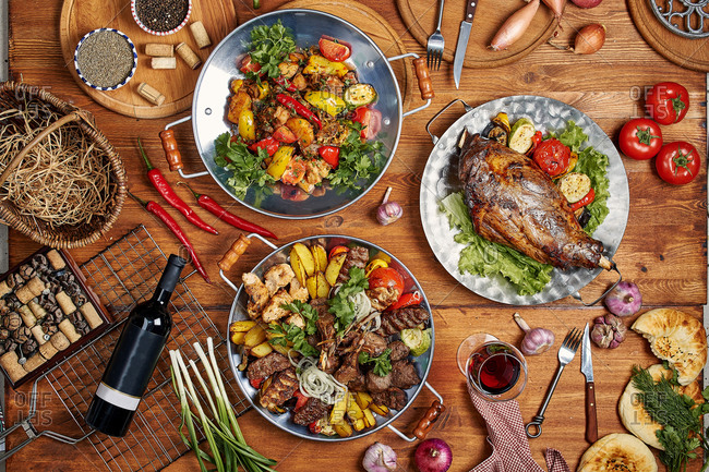 Lula kebabs, grilled vegetables, and pork knuckle with red wine