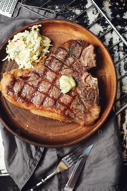 T-bone grilled steak with butter and coleslaw salad