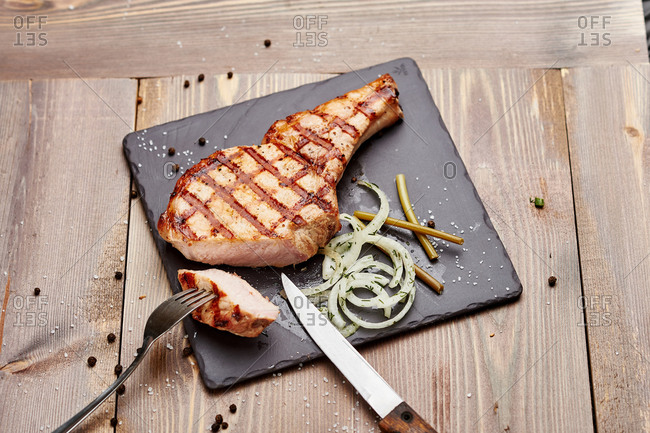 Grilled pork steak with pickled onions