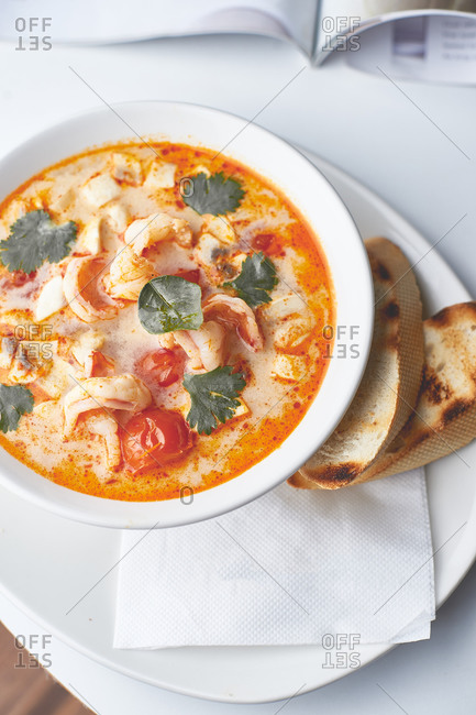 Asian tom yam kung soup with baguette toast