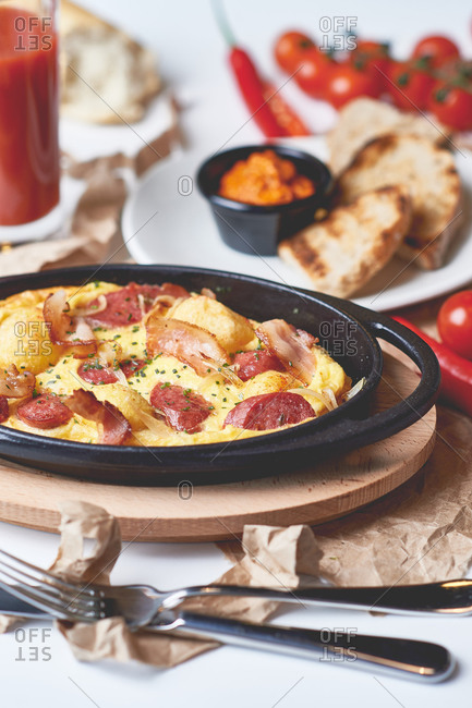 Omelet with bacon, sausage, pepperoni, and toast with guacamole and tomato juice