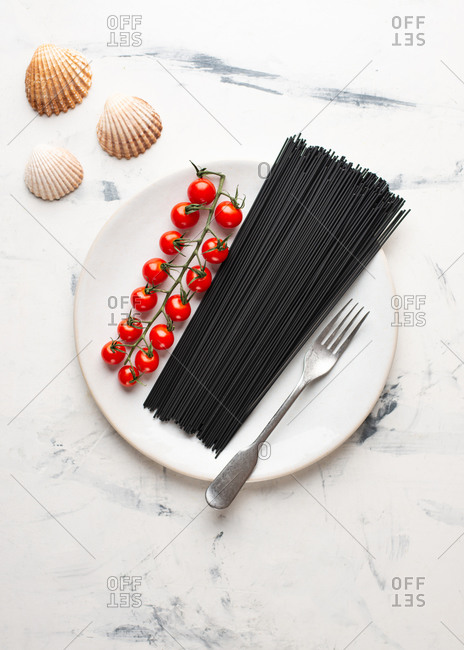 Overhead view of black spaghetti and fresh cherry tomatoes on white ceramic plate