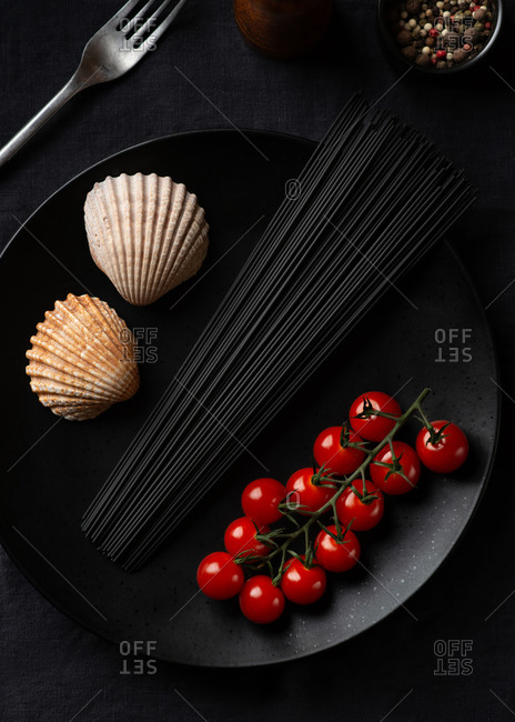 Overhead view of black spaghetti and fresh cherry tomatoes served on black ceramic plate