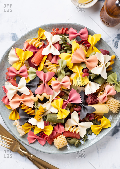 Overhead view of plate with uncooked colorful various types Italian pasta