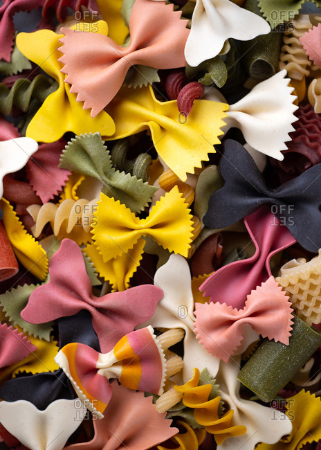 Overhead close-up image of uncooked colorful various types Italian pasta