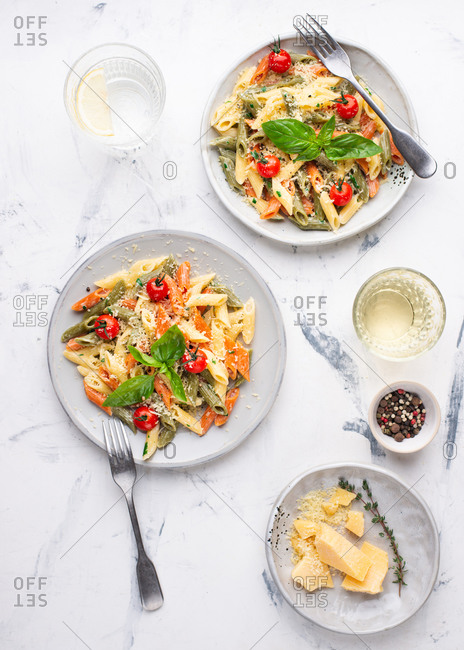 Overhead view of two plates of pasta penne with cream sauce, cherry tomatoes and basil