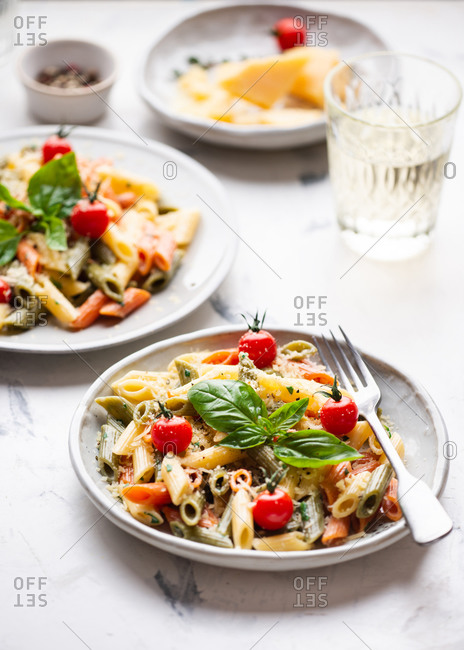 Plate of pasta penne with cream sauce, cherry tomatoes and fresh basil