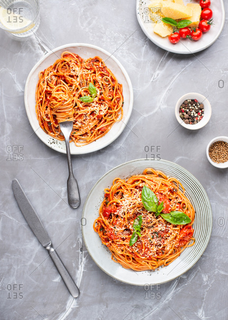 Overhead view of two plates of spaghetti with tomato sauce, cheese and fresh basil