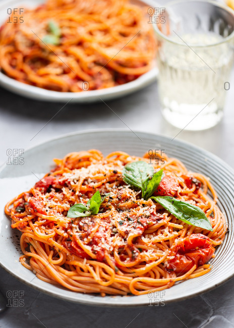 Plate of spaghetti with tomato sauce, cheese and fresh basil leaves