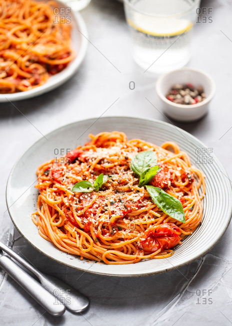 Plate of spaghetti with tomato sauce, cheese and fresh basil leaf