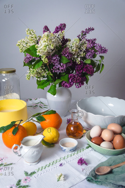 Fresh lilacs on a table with ingredients to make Easter bread