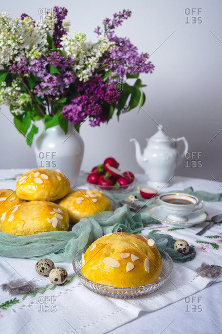 Freshly baked sweet Easter bread (pinca) on the table with flowers and coffee