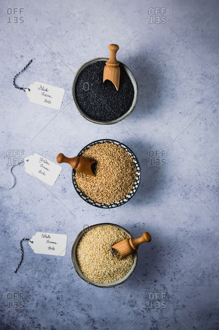 Three types of sesame seeds in small ceramic bowls with labels