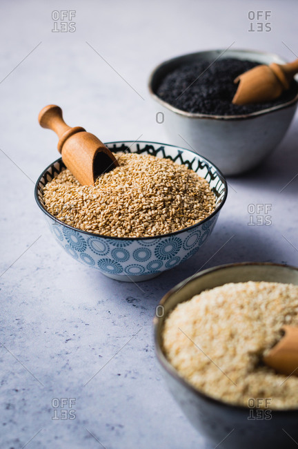 Three types of sesame seeds in small ceramic bowls