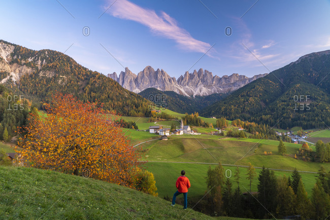 Rear view of man admiring the Odle peaks and little village of Santa Magdalena in autumn, Funes, Dolomites, South Tyrol, Italy, Europe