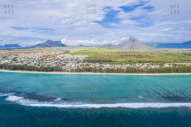 Aerial view by drone of waves crashing on Flic en Flac beach with Piton de la Petite Riviere Noire mountain, Mauritius, Indian Ocean, Africa
