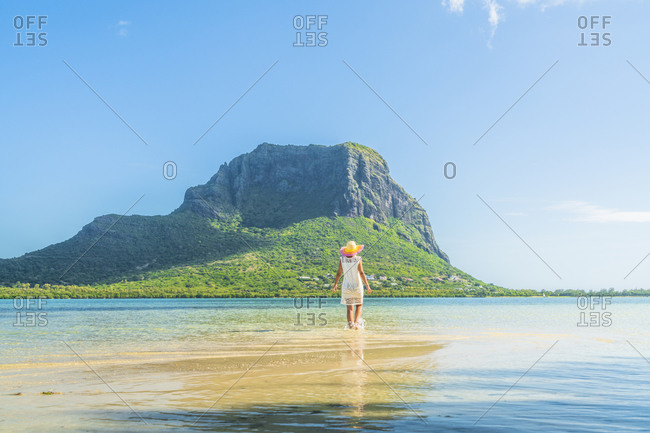 Woman admiring Le Morne mountain standing in the shallow water of turquoise lagoon, La Gaulette, Mauritius, Indian Ocean, Africa
