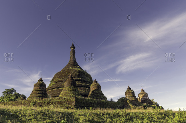 Looking up at the main stupa with satellite stupas of Andaw Thein pagoda with a few wispy clouds in a blue sky above, Mrauk U, Rakhine, Myanmar (Burma), Asia