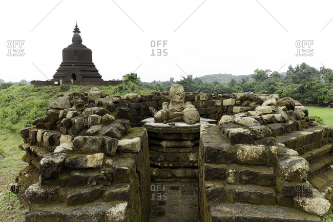 A ruined stone stupa with damaged Buddha statue in the centre, with West Myatazaung Pagoda in the background, Mrauk U, Rakhine, Myanmar (Burma), Asia