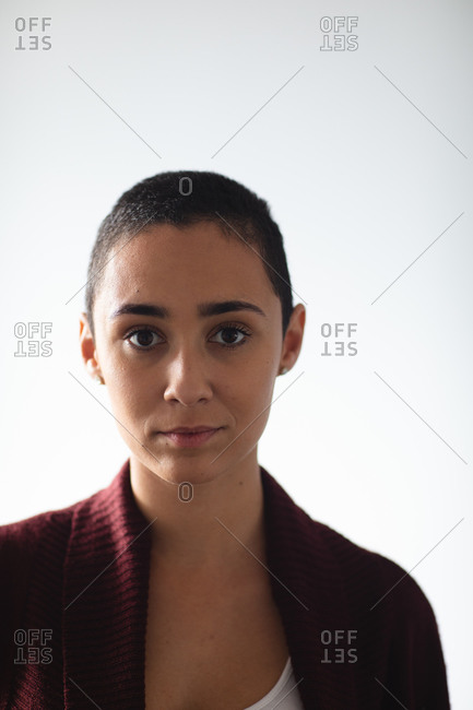 Portrait close up of a mixed race woman with short hair wearing a cardigan, looking straight to camera at home