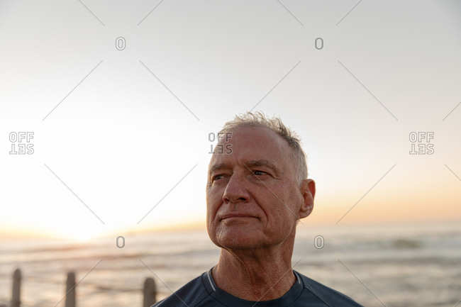 Front view of a mature senior Caucasian man working out on a promenade, admiring the view during sunset