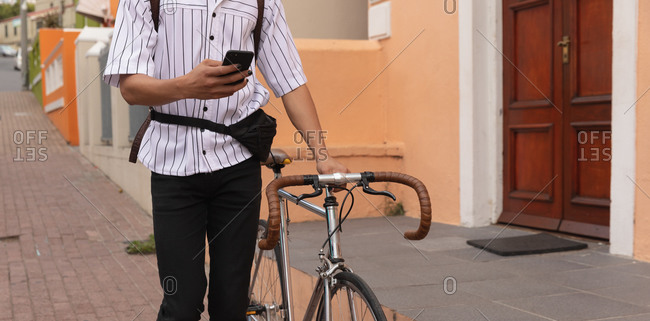 Front view mid section of a mixed race man with long dreadlocks out and about in the city on a sunny day, walking the street using a smartphone and wheeling his bicycle.