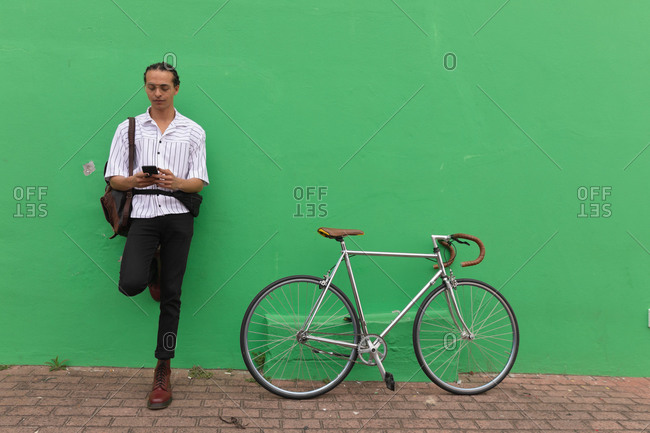 Front view of a mixed race man with long dreadlocks out and about in the city on a sunny day, standing in the street, leaning against the green wall, using a smartphone, with his bicycle standing next to him.