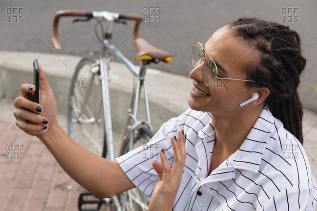 Side view close up of a mixed race man with long dreadlocks out and about in the city on a sunny day, sitting in the street wearing headphones, using a smartphone and waving his hand, with his bicycle standing next to him.