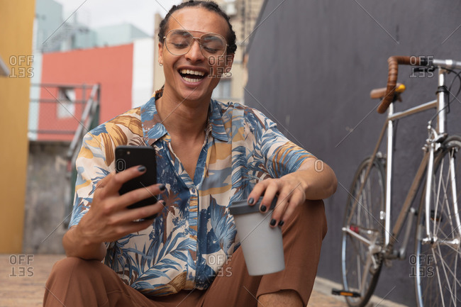 Front view close up of a mixed race man with long dreadlocks out and about in the city on a sunny day, sitting in the street and smiling, using a smartphone and holding a cup of coffee, with his bicycle standing next to him.