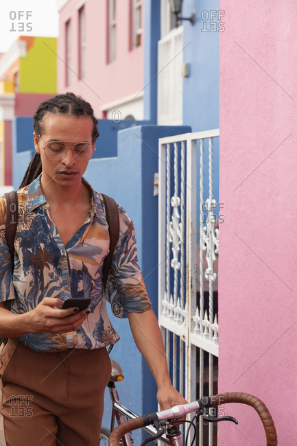 Front view of a mixed race man with long dreadlocks out and about in the city on a sunny day, walking the street using a smartphone and wheeling his bicycle.
