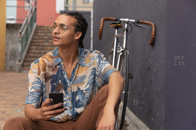 Front view close up of a mixed race man with long dreadlocks out and about in the city on a sunny day, sitting in the street, using a smartphone, with his bicycle leaning against the wall next to him.