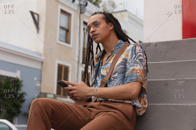 Front view close up of a mixed race man with long dreadlocks out and about in the city on a sunny day, sitting on the stairs in the street and using a smartphone, looking straight into camera.