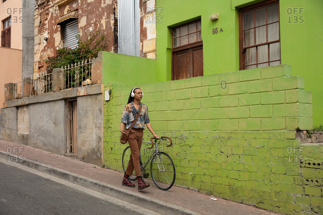 Front view of a mixed race man with long dreadlocks out and about in the city on a sunny day, wearing headphones, walking the street and wheeling his bicycle.