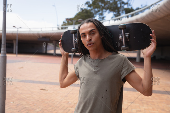 Front view of a mixed race man with long dreadlocks out and about in the city on a sunny day, standing in the street next to a bridge, holding a skateboard and looking straight into camera.