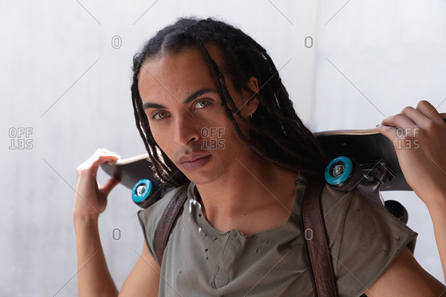 Front view close up of a mixed race man with long dreadlocks out and about in the city on a sunny day, holding a skateboard and looking straight into camera.