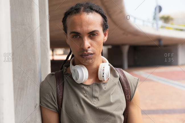 Portrait of a mixed race man with long dreadlocks out and about in the city on a sunny day, standing in the street by a bridge and looking straight into a camera