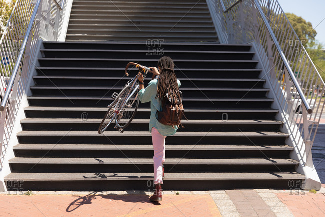Rear view of a mixed race man with long dreadlocks out and about in the city on a sunny day, going upstairs holding his bicycle