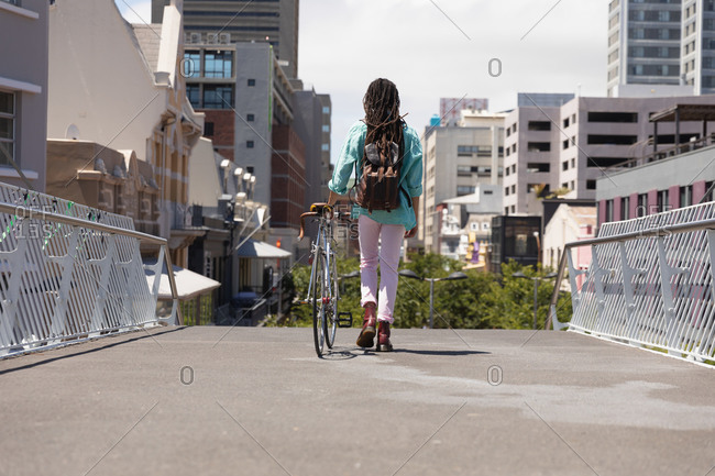 Rear view of a mixed race man with long dreadlocks out and about in the city on a sunny day, wearing backpack, walking the street and wheeling his bicycle.