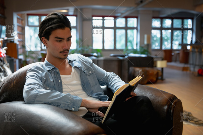 Side view of a young mixed race man enjoying time at home, resting in his sitting room, sitting in the armchair, reading a book.