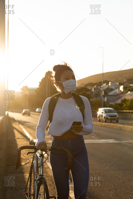 Front view of a mixed race woman with long dark hair out and about in the city streets during the day, wearing a face mask against air pollution and coronavirus, walking with her bicycle and using a smartphone with urban road traffic in the background.